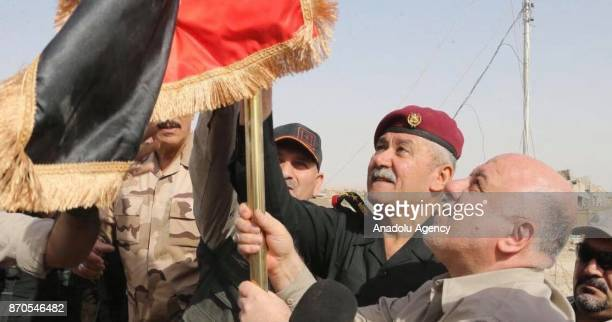 Iraqi Prime Minister Haider alAbadi hangs an Iraqi flag during his visit Qaim town and Husaybah border gate newlyliberated town from Daesh terrorists...