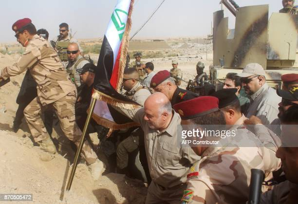 Iraqi Prime Minister Haider alAbadi prepares to erect a national flag in AlQaim on November 5 after troops retook the border town from Islamic State...
