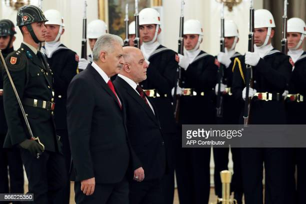 Iraqi Prime Minister Haider AlAbadi walks with Turkish Prime Minister Binali Yildirim during an official welcoming ceremony at the Cankaya Palace in...