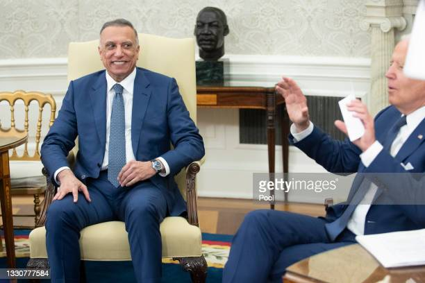 Iraqi Prime Minister Mustafa Al-Kadhimi listens as U.S. President Joe Biden speaks during a bilateral meeting in the Oval Office at the White House...