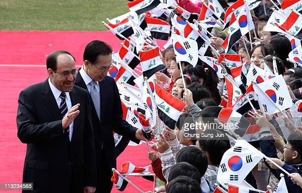 Iraqi Prime Minister Nouri alMaliki and South Korean President Lee MyungBak greet South Korean children during a welcoming ceremony held at the...