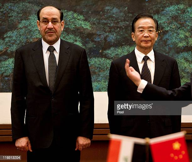 Iraqi Prime Minister Nouri alMaliki left stands with Chinese Premier Wen Jiabao as they attend a signing ceremony at the Great Hall of the People on...