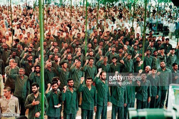 Iraqi Prisoner of War pray next to an Iranian Revolutionary Guard during Friday noon prayers at Tehran University on June 29 1990 / AFP PHOTO / Mike...