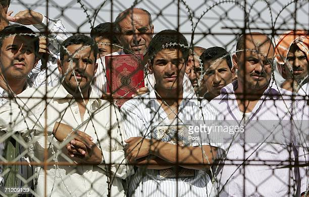 Iraqi prisoners wait inside the compound shortly before they are released as another batch of 200 prisoners are freed from Abu Ghraib prison on June...