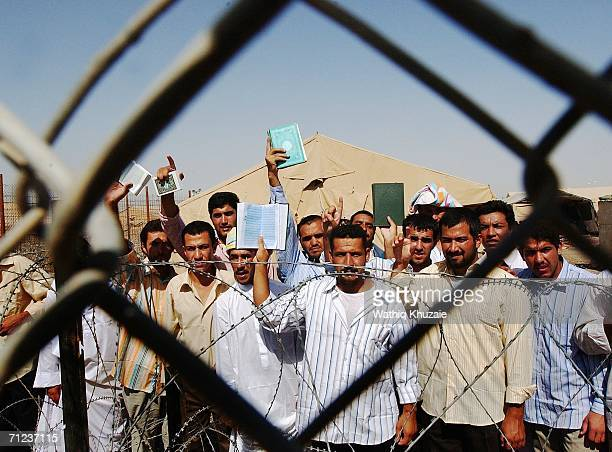 Iraqi prisoners wave and hold copies of the holy Quran as they wait to be released on June 19 2006 at Abu Ghraib prison west of Baghdad Iraq More...