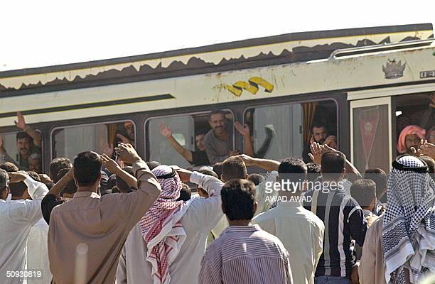 Iraqi prisoners wave to their waiting relatives and friends from the windows of a bus as they are transported out of the Abu Ghraib prison following...