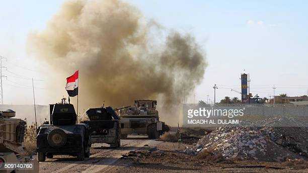 Iraqi progovernement forces drive their armoured vehicles in the Jwaibah area on the eastern outskirts of Ramadi on February 8 after they retook the...