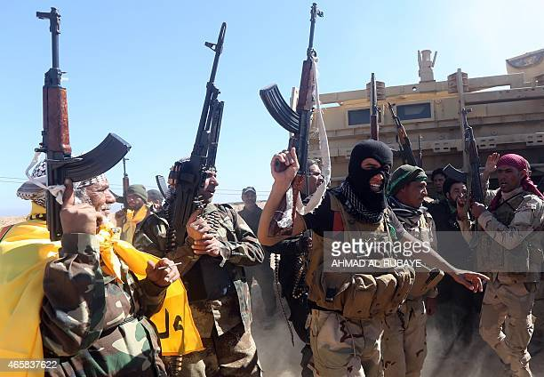 Iraqi pro-government fighters celebrate as they advance into Tikrit, 160 kms north of Baghdad, during a military operation to regain the city from...