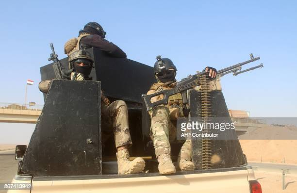 Iraqi progovernment forces are seen on the back of an armed pick up truck as they advance towards the town of Rawa on the Euphrates river during...