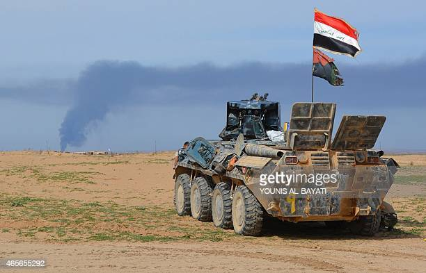 Iraqi progovernment forces hold a position in AlAlam village northeast of the multiethnic city of Tikrit on March 8 during a military operation to...