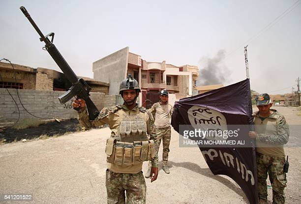 Iraqi progovernment forces hold an Islamic State group flag in the alDhubat II neighbourhood of Fallujah as they try to clear the city of IS fighters...
