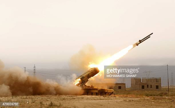 Iraqi progovernment forces including fighters from the Shiite Muslim AlAbbas popular mobilisation unit fire a rocket during an operation to retake...