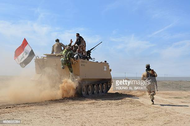 Iraqi pro-government forces sit on armoured personnel carrier driving near the Al-Alam village, northeast of the multi-ethnic city of Tikrit, on...