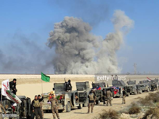 Iraqi progovernment forces stand next to armored vehicles as they take position in alAramil area south of the Anbar province's capital Ramadi during...