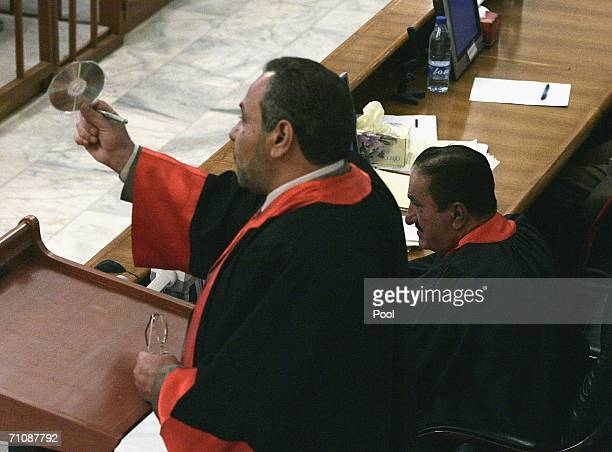 Iraqi prosecution lawyer Jafar alMusawi shows to the court an audio compact disc containing a prosecutor's interview during the trial of former Iraqi...