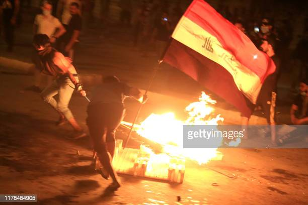 Iraqi protesters burn items to block the road as they clash with security forces during an anti-government demonstration in the Shiite shrine city of...