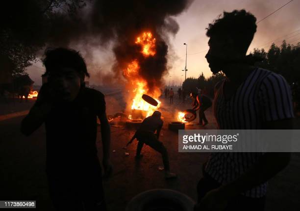TOPSHOT Iraqi protesters burn tyres during a demonstration against state corruption failing public services and unemployment in the Iraqi capital...