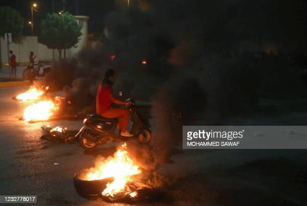 Iraqi protesters burn tyres in front of the Karbala governorate headquarters in the central city of Karbala, early on May 9 following the reported...