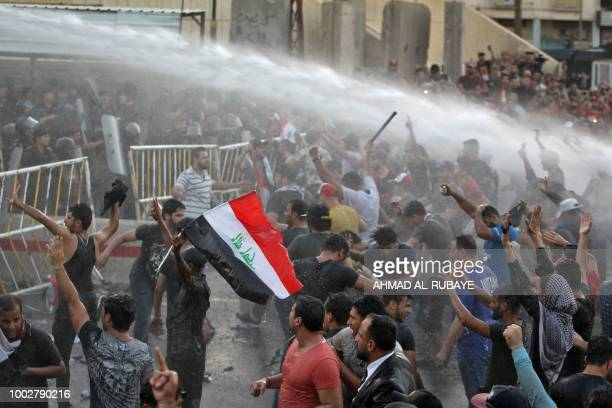 Iraqi protesters chant slogans and wave national flags are being sprayed with water cannon by security forces during clashes at a demonstration...