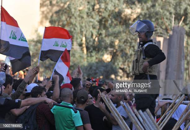 Iraqi protesters chant slogans and wave national flags by security forces during a demonstration against unemployment and a lack of basic services in...