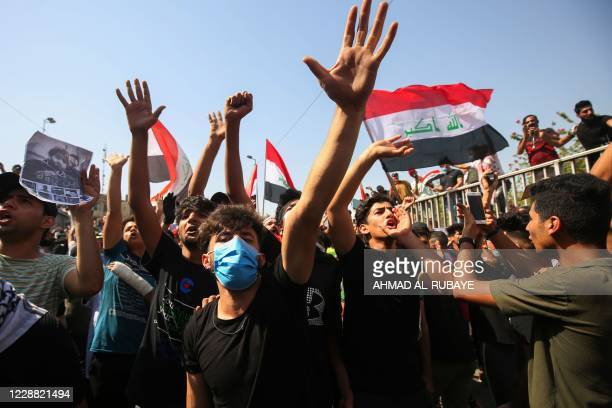 Iraqi protesters chant slogans and wave the national flag during a demonstration in Tahrir Square in the centre of Iraq's capital Baghdad on October...