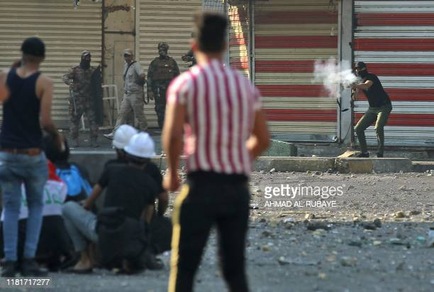 Iraqi protesters clash with Iraqi security forces at Baghdad's Khallani square during ongoing antigovernment demonstrations on November 11 2019 The...