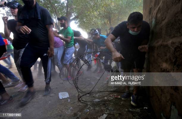 TOPSHOT Iraqi protesters flee from security forces during a demonstration against state corruption failing public services and unemployment in the...