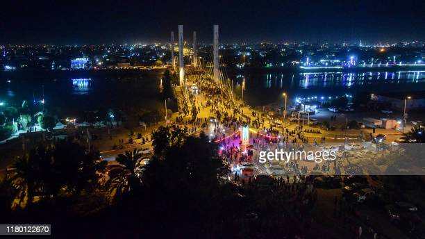Iraqi protesters gather late at night during an antigovernment demonstration by the Hadarat bridge across the Euphrates river in Nasiriyah the...
