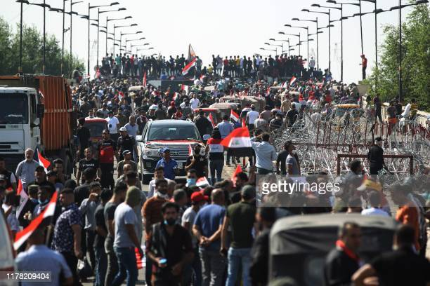 Iraqi protesters gather on the capital Baghdad's Al-Jumhuriyah Bridge on October 26 during an anti-government protest. - Iraqi security forces fired...