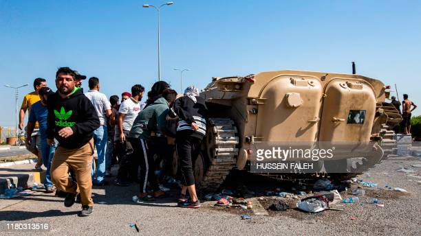 Iraqi protesters gather outside an abandoned army armoured personnel carrier at a demonstration outside the southern port of Umm Qasr on November 5...