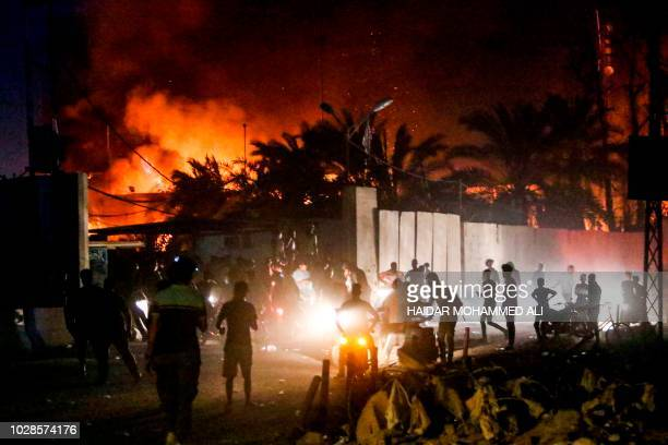 Iraqi protesters gather outside the burning headquarters of the Iranian consulate in the southern city of Basra on September 7 2018 during...