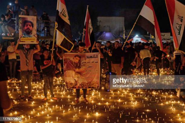Iraqi protesters hold a candlelight vigil for victims killed during anti-government demonstrations in the Shiite shrine city of Karbala, south of...