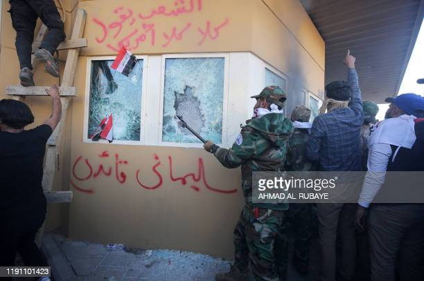 Iraqi protesters including members the Hashed alShaabi a mostly Shiite network of local armed groups trained and armed by powerful neighbour Iran...