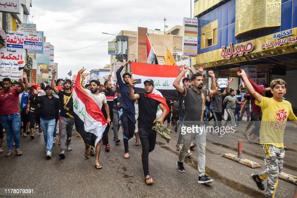 Iraqi protesters march with national flags during an anti-government demonstration in Nasiriyah, the capital of the southern province of Dhi Qar on...