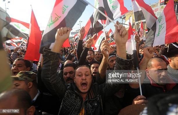 Iraqi protesters most of them members of Shiite paramilitary forces wave national flags during a demonstration in Baghdad's Tahrir Square on December...