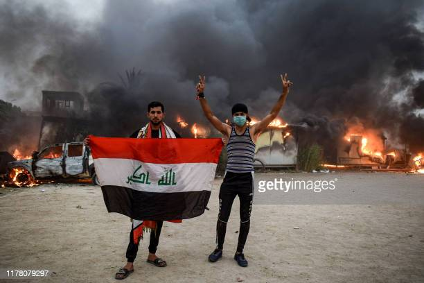 Iraqi protesters pose with a national flag during an anti-government demonstration outside the burning local government headquarters in Nasiriyah,...
