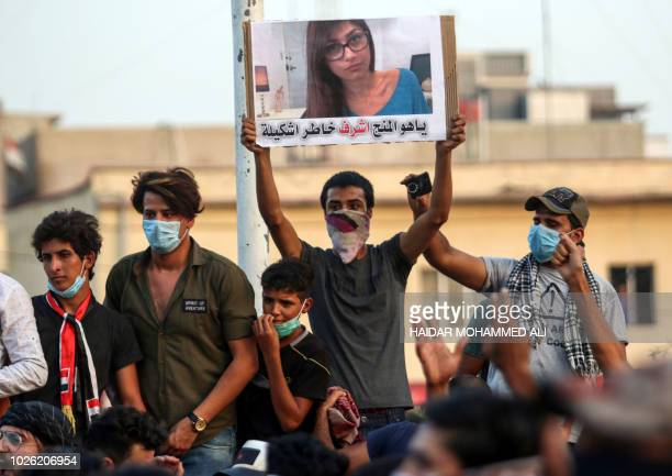 Iraqi protesters raise a sign bearing the image of Lebanese American pornstar Mia Khalifa with a caption below reading in Iraqi vernacular Arabic...