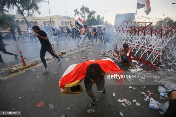 TOPSHOT Iraqi protesters run for cover from teargas canisters fired by security forces during an antigovernment demonstration on AlJumhuriya Bridge...