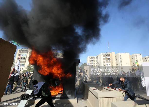 TOPSHOT Iraqi protesters set ablaze a sentry box in front of the US embassy building in the capital Baghdad to protest against the weekend's air...