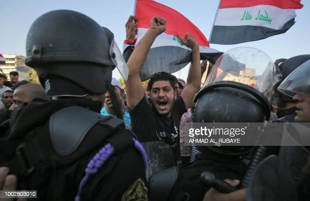 Iraqi protesters shout slogans and wave national flags as they facing security forces during clashes at a demonstration against unemployment and a...