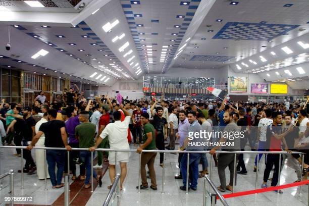 Iraqi protesters shout slogans as they demonstrate inside the terminal in Najaf International Airport in the central shrine city on July 13 against...