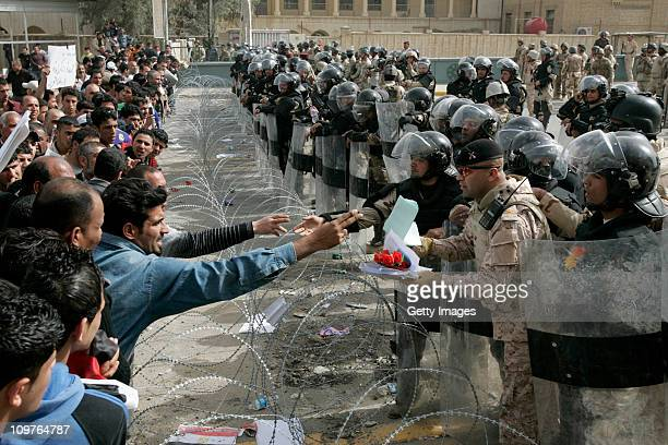 Iraqi protesters speak with riot policmen as they take part in an anti-government demonstration on March 4, 2011 at Tahrir Square in Baghdad, Iraq....