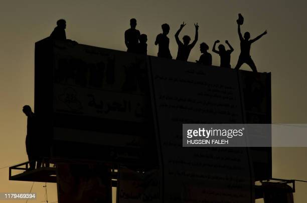 Iraqi protesters stand on a billboard during ongoing anti-government demonstrations in the southern city of Basra on November 2, 2019. - Iraqi...
