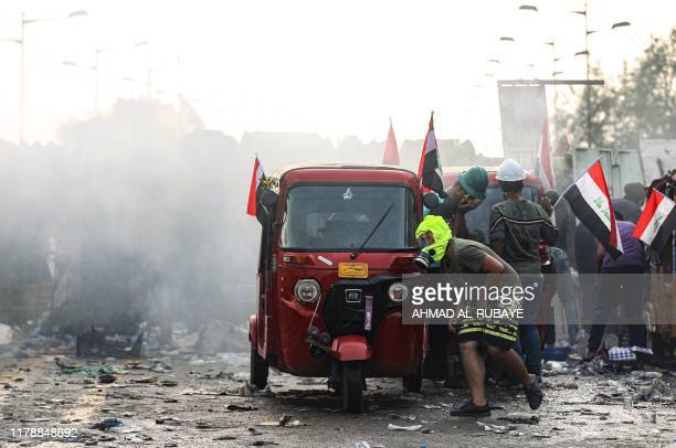 Iraqi protesters take cover behind a tuk-tuk in clashes with security forces amidst demonstrations on al-Jumhuriya bridge which connects between the...