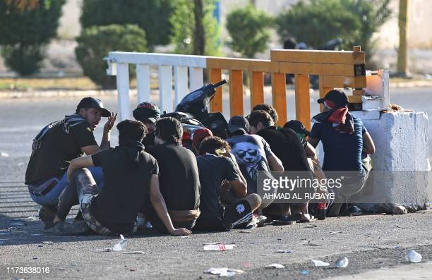 Iraqi protesters take cover during a demonstration against state corruption failing public services and unemployment in the Iraqi capital Baghdad's...