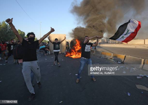 TOPSHOT Iraqi protesters take part in a demonstration against state corruption failing public services and unemployment in the Iraqi capital...