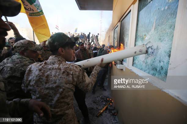Iraqi protesters use a plumbing pipe to break the bullet-proof glass of the US embassy's windows in Baghdad, as thousands of angry Iraqis, including...