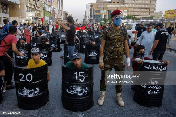 Iraqi protesters use half barrels as shields during an anti-government demonstration in the central shrine city of Najaf on June 3 despite the...