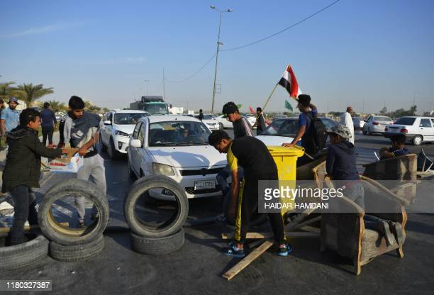Iraqi protesters use tyres to block the road to Najaf airport in the during continuing antigovernment protests in the central Iraqi holy city on...