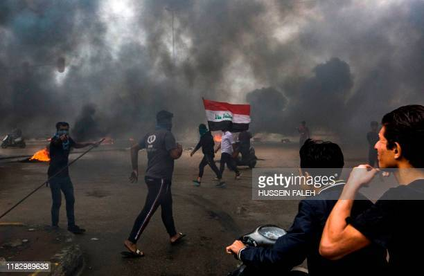 Iraqi protesters walk and ride scooters past burning tires blocking a road during a demonstration in the southern city of Basra on November 17 as...
